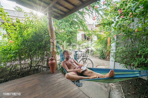 Young man on hammock reading book on patio in hotel in a tropical place enjoying vacations and relaxation time
