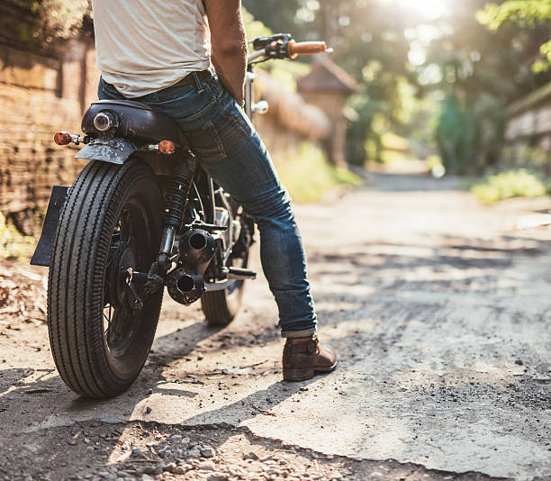 young man on his motorcycle on dirt road - motorrad männer stock-fotos und bilder