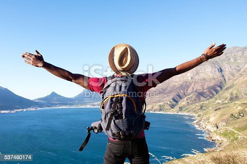 istock Young man on holiday standing with arms spread open 537460174