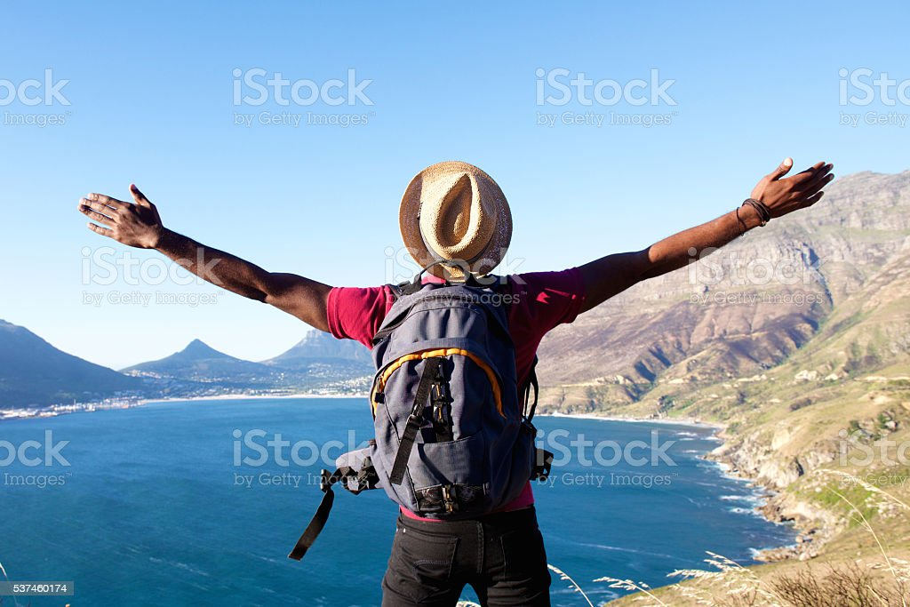 Young man on holiday standing with arms spread open stock photo