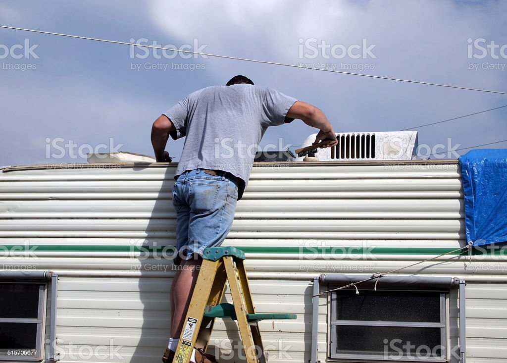 Young man on ladder working on trailer of trailer photo. stock photo