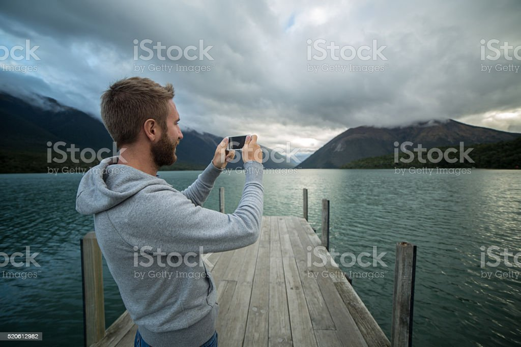 Young man on lake pier takes picture using mobile phone stock photo