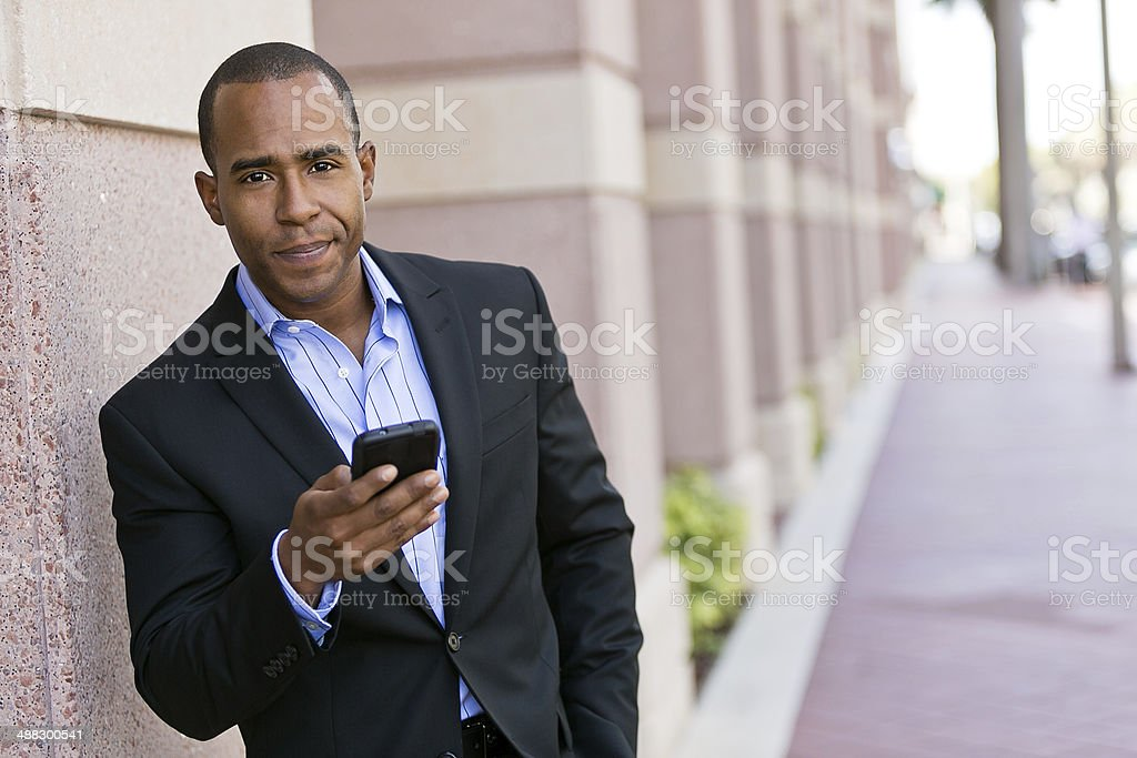 Young man on mobile device stock photo