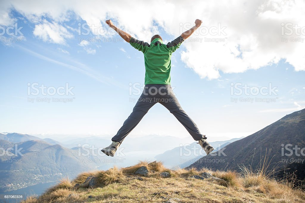 Young man on mountain top jumps for joy and success stock photo