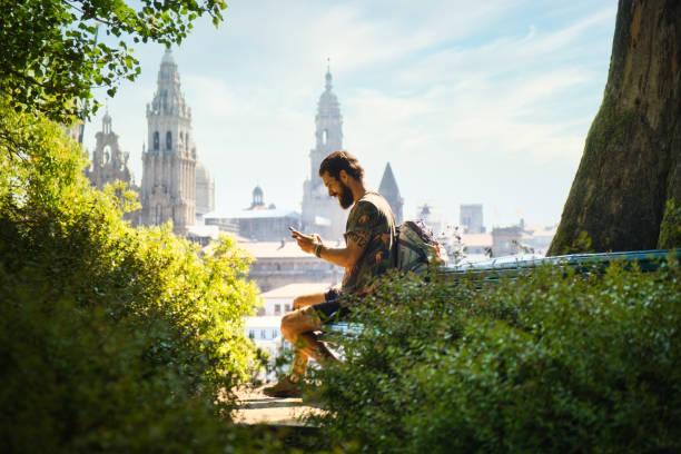 Junger Mann auf Pilgerreise in Santiago de Compostela mit Telefon – Foto