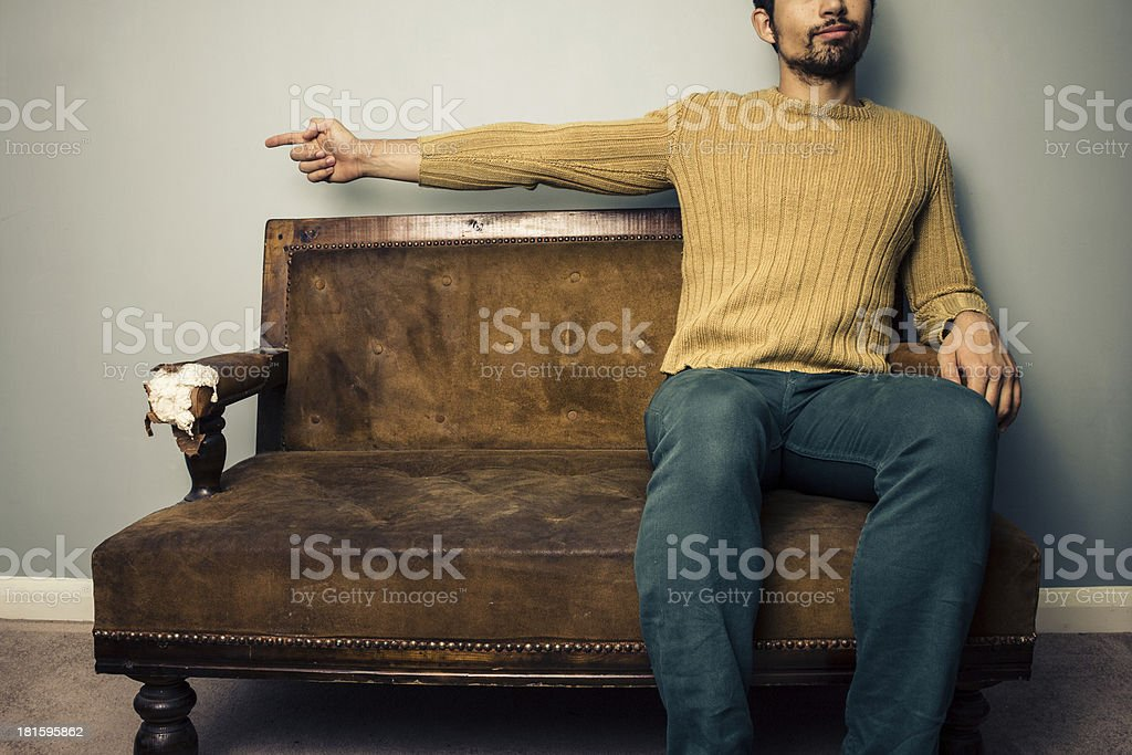 Young man on sofa pointing left royalty-free stock photo