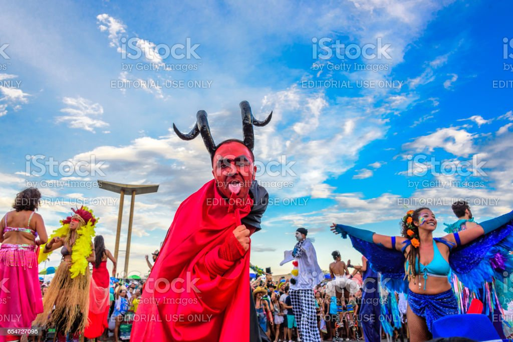 Young man on stilts in a costume of devil licking his tail at Bloco Orquestra Voadora, Carnaval 2017 stock photo