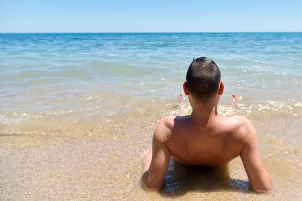 junger mann am strand - fkk strand stock-fotos und bilder