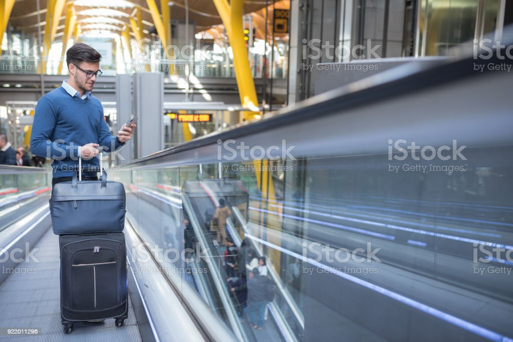 young man on the escalator at the airport using his mobile phone with his luggage smiling stock photo