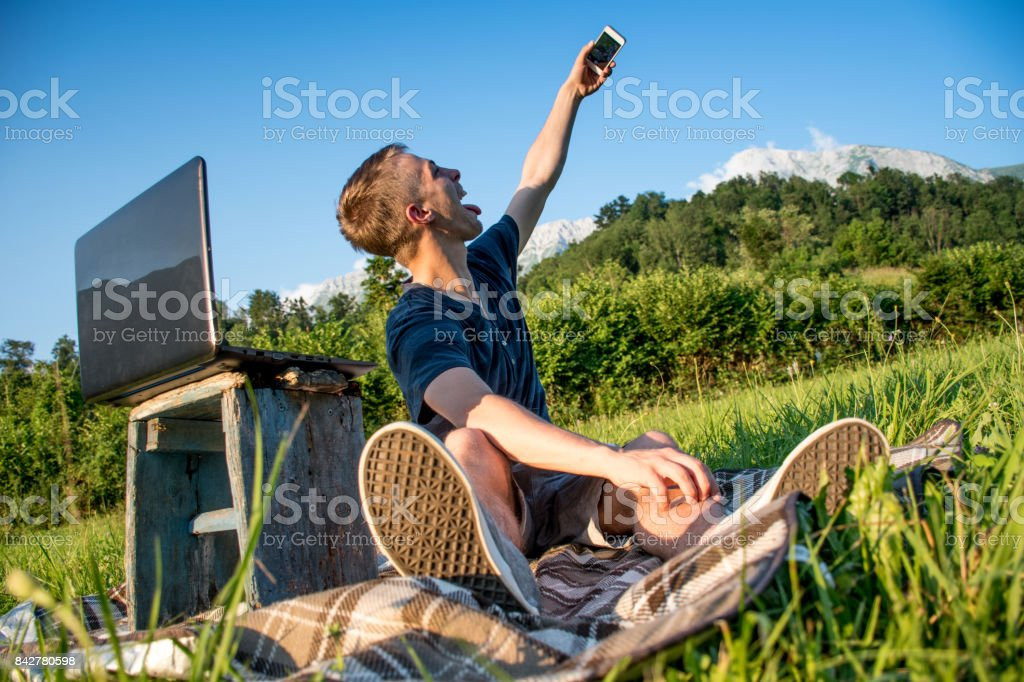 Young Man On The Mountain Meadow Taking Selfie And  Using Laptop To Be Connected With The Rest Of The World stock photo