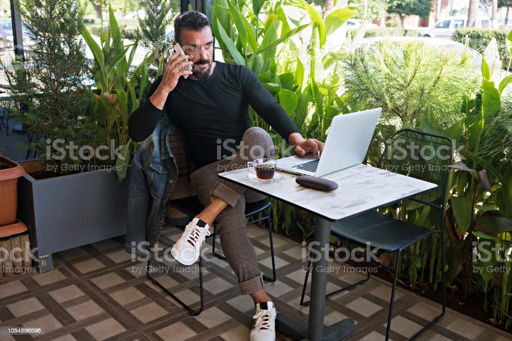 Genç adam bir kafede telefonda stok fotoğrafı