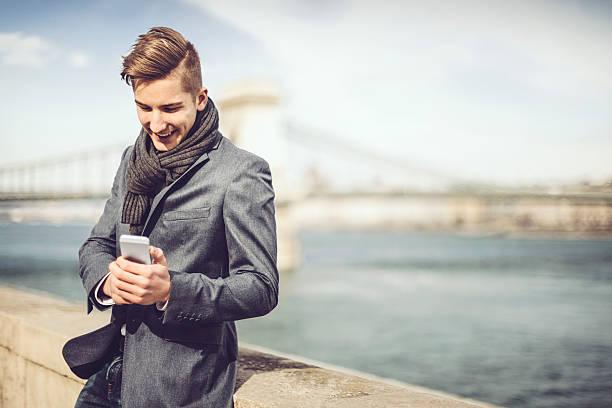 junger mann am telefon - mode herbst 2015 stock-fotos und bilder