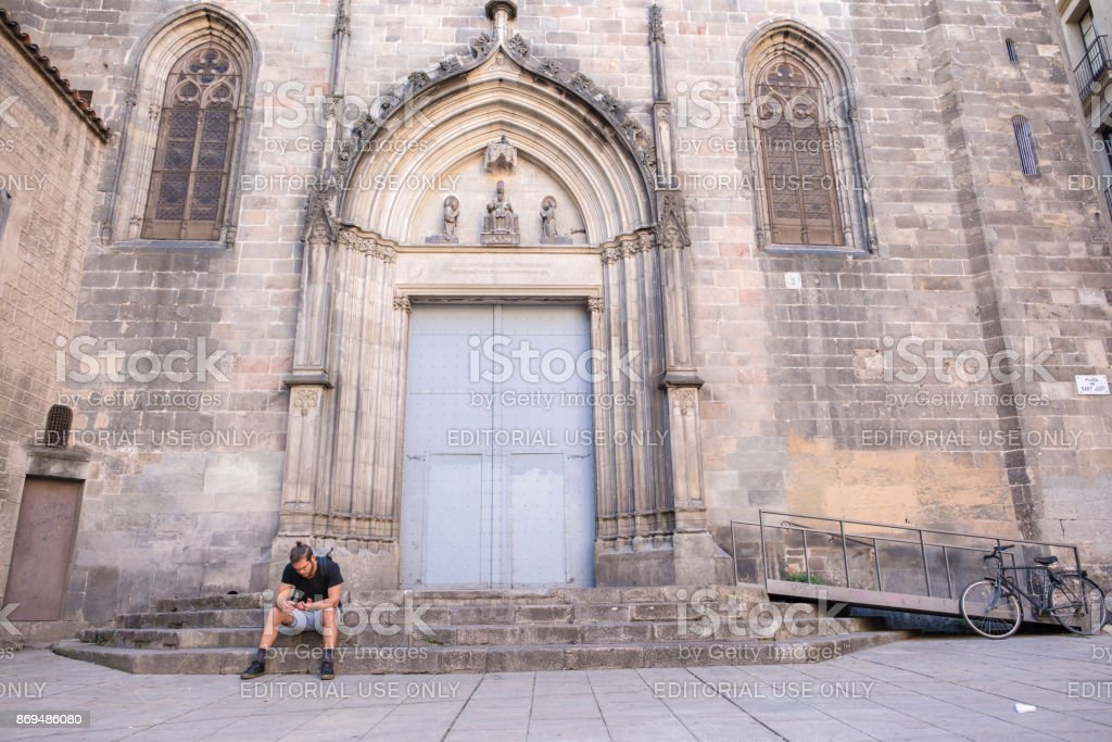 Young man on the steps of Cathedral of Martyrs Just and Pastor in Barcelona stock photo
