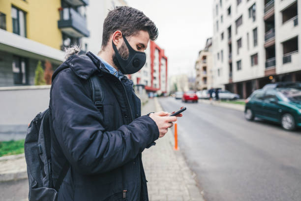 Young man on the street wearing anti-pollution mask Young man wearing anti-smog mask for health protection against air pollution in the city. Texting on his mobile phone. City pollution concept antipollution stock pictures, royalty-free photos & images