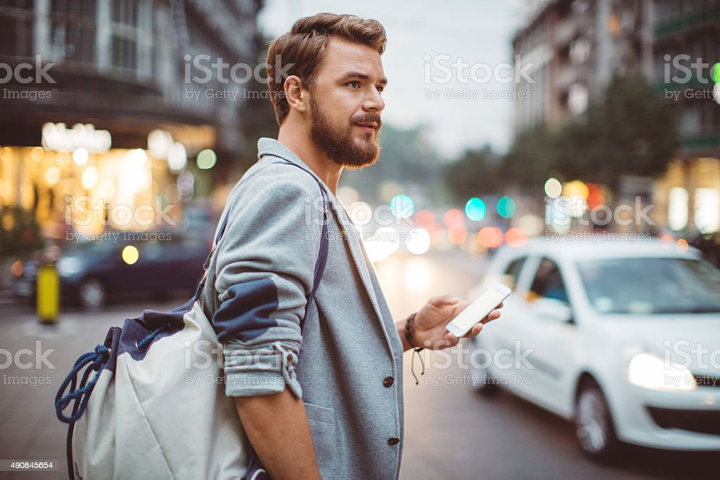 Young man on the streets of big city. Young man on the street of big city ,   waiting taxi,   chacking his smartphone,   for news or new messages.   Or looking for map instructions.  Carry backpack on one shoulder.  Dusk time.   Casual dressed.   Street lights in background. 20-29 Years Stock Photo