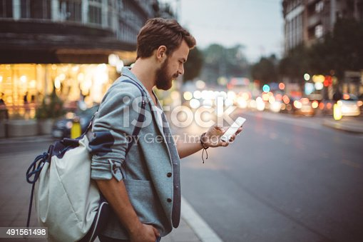 Young man on the street of big city , waiting taxi, chacking his smartphone,  for news or new messages.  Or looking for map instructions. Carry backpack on one shoulder.  Dusk time.  Casual dressed. Street lights in background.