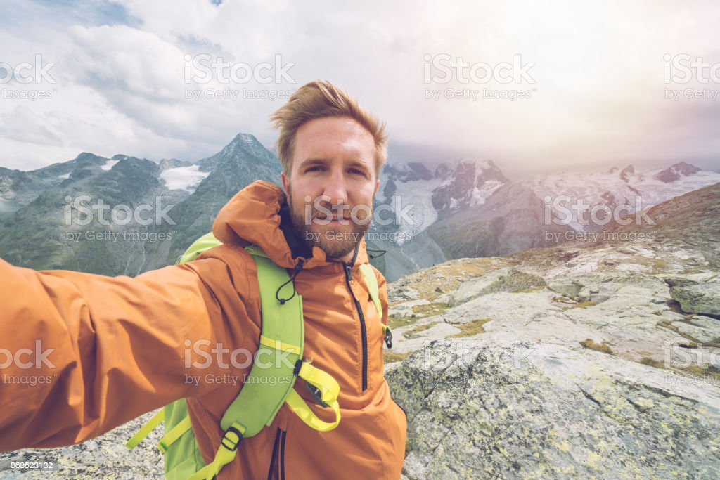 Young man on top of mountain trail takes selfie portrait, Switzerland stock photo