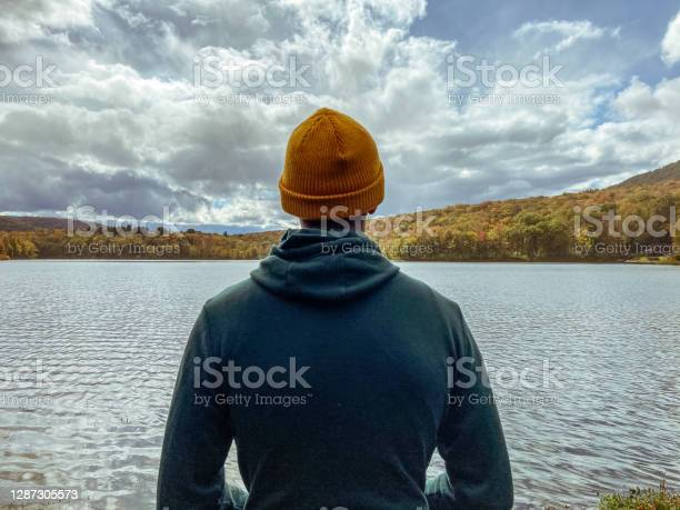 Photo of Young man only stands in contemplation looking at the view of a beautiful lake surrounded by trees with vibrant fall colors.