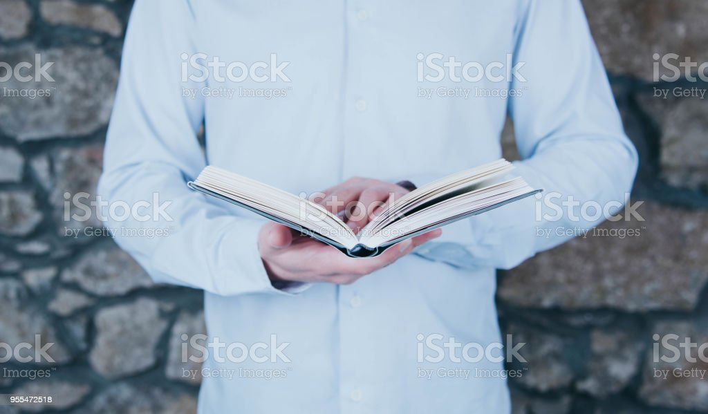 Young man opening and reading a book