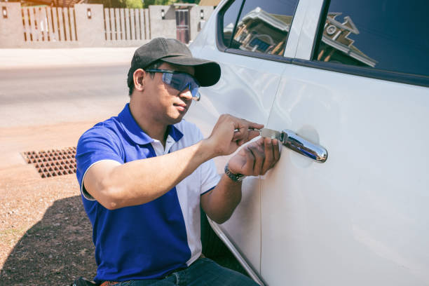 Young Man Opening White Car Door With Lockpicker. Young Man Opening White Car Door With Lockpicker. Professional making key in locksmith locksmith stock pictures, royalty-free photos & images