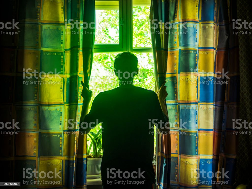 young man opens curtains on the window on the sunny summer morning - Zbiór zdjęć royalty-free (Balkon)