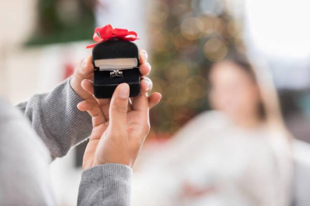 junger mann öffnet verlobungsring - verlobung was schenken stock-fotos und bilder