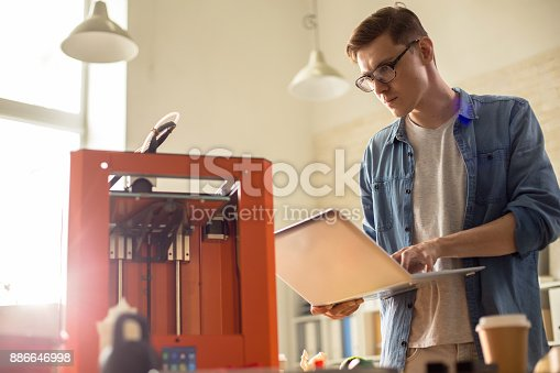 886646936 istock photo Young Man Operating 3D Printer 886646998