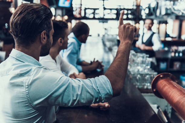 Young Man Ordering One Beer with Hand in Bar. stock photo