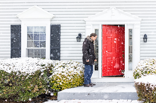 Young man outside front yard red door of house with snow during blizzard white storm, snowflakes falling letting calico cat outside outdoors to porch