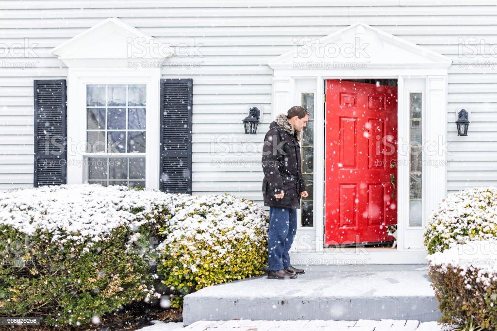 Jovem jardim vermelho na porta de casa com neve durante tempestade de nevasca branco, flocos de neve caindo deixar gato malhado fora ao ar livre na varanda - foto de acervo