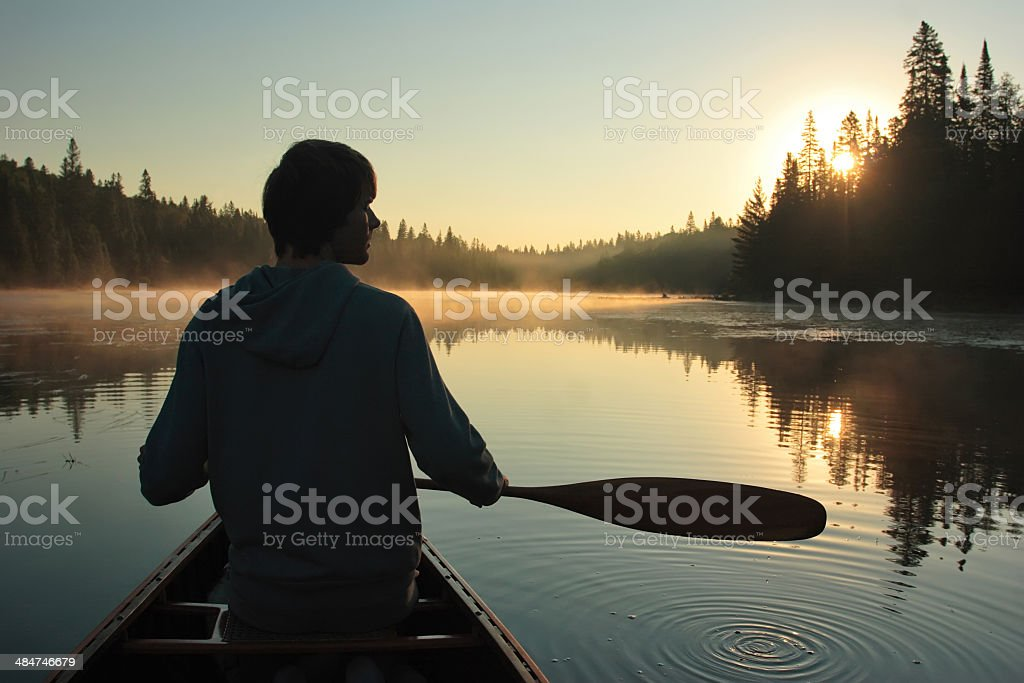 Young man paddling a canoe at sunset stock photo