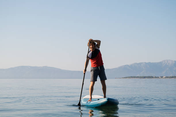 Young man paddling on sup board stock photo