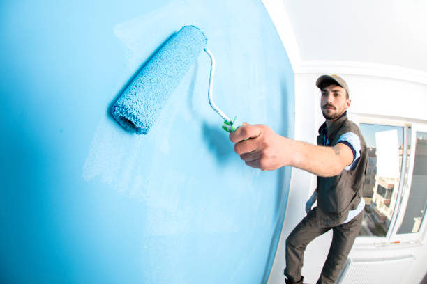 young man painting a wall blue with a roller - painter stock photos and pictures