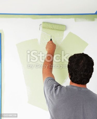 A left-handed young man is painting a bedroom wall green with a paint roller. Blue masking tape outlines the ceiling and window frame at left for protection against potential spatters and slips.