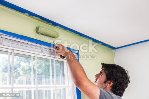 A left-handed young man is painting a bedroom wall between the ceiling and a window with a green paint roller. Blue masking tape outlines the ceiling and window frame for protection against potential spatters and slips.
