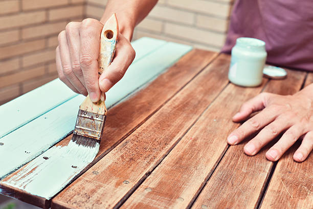 young man painting an old wooden table stock photo
