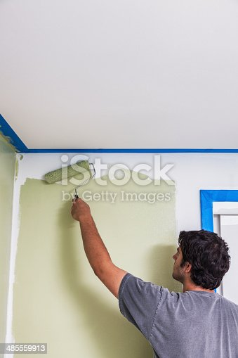 A left-handed young man is using a paint roller to paint a bedroom wall near one corner of the room. The blue masking tape protects the ceiling and closet frame to his right from potential spatters and slips.