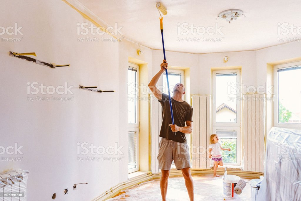 Young man painting ceiling with telescopic roller stock photo