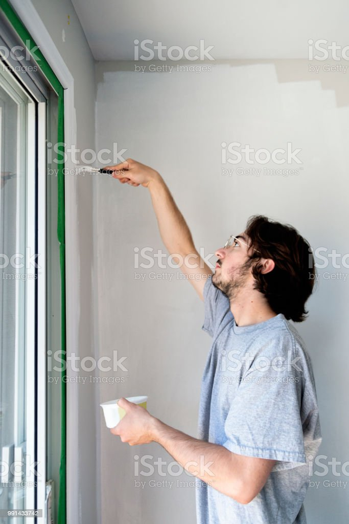 Young man painting living room in first appartement. stock photo