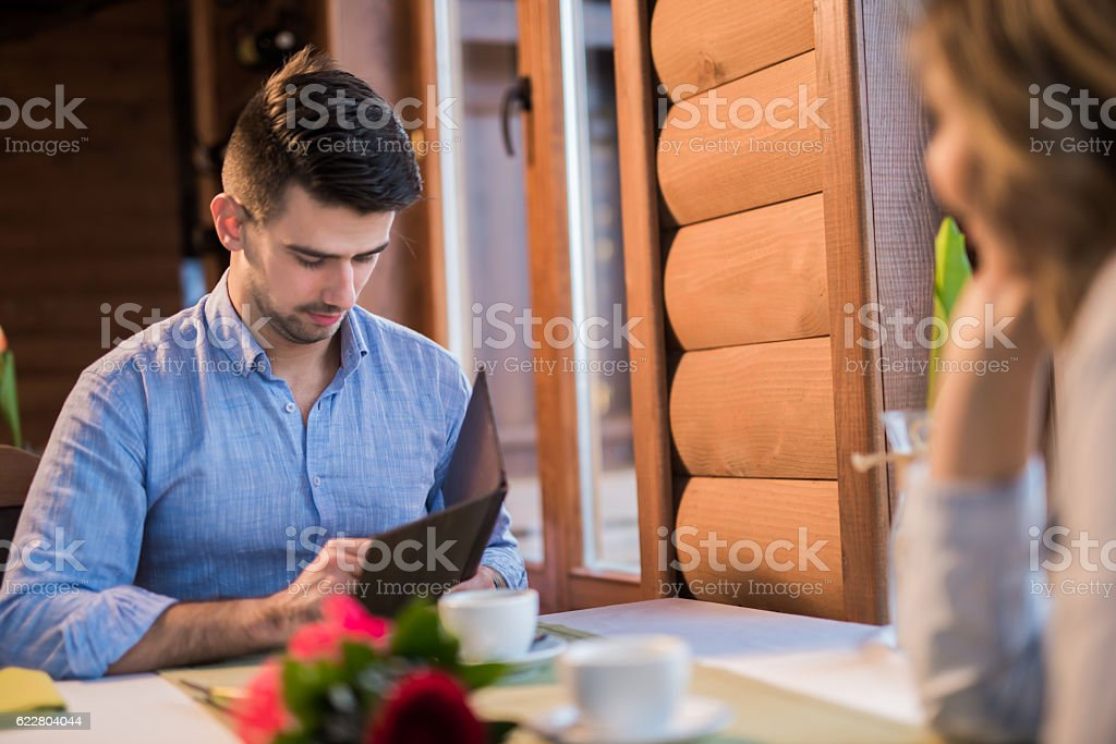 Young man paying a bill in the restaurant stock photo
