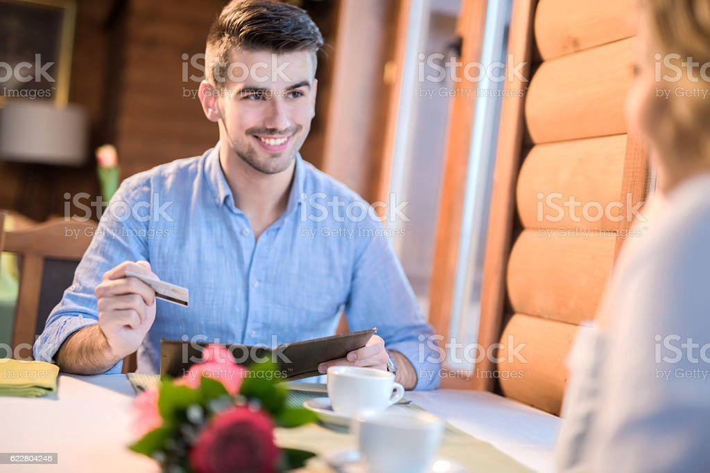 Young man paying a bill with a credit card stock photo