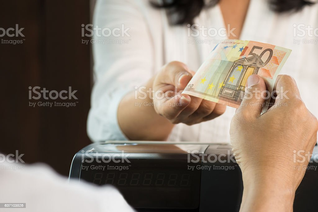 Young man paying cash at retail shop. stock photo