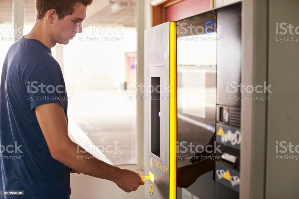 Young Man Paying For Car Parking At Machine stock photo
