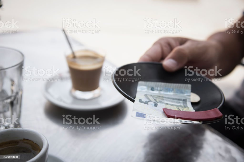 young man paying the bill in the terrace of a cafe stock photo