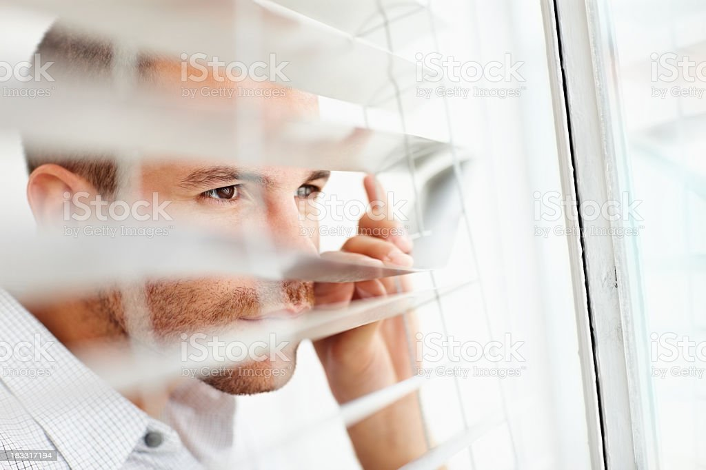 Young man peeking out of the window blinds royalty-free stock photo