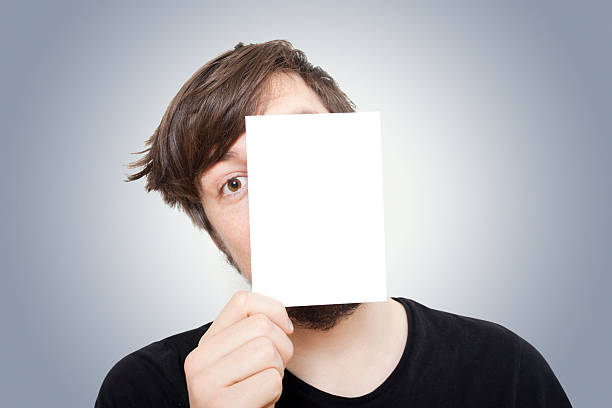 Young Man Peeping from behind a Piece of Paper stock photo
