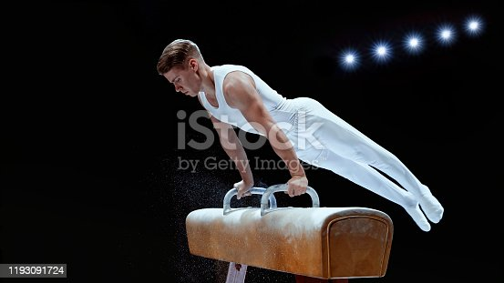 Young male gymnast performing on pommel horse against black background.