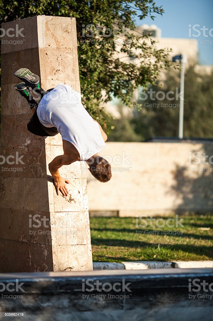 Young athlete showing skills of free running. Parkour trick with city...