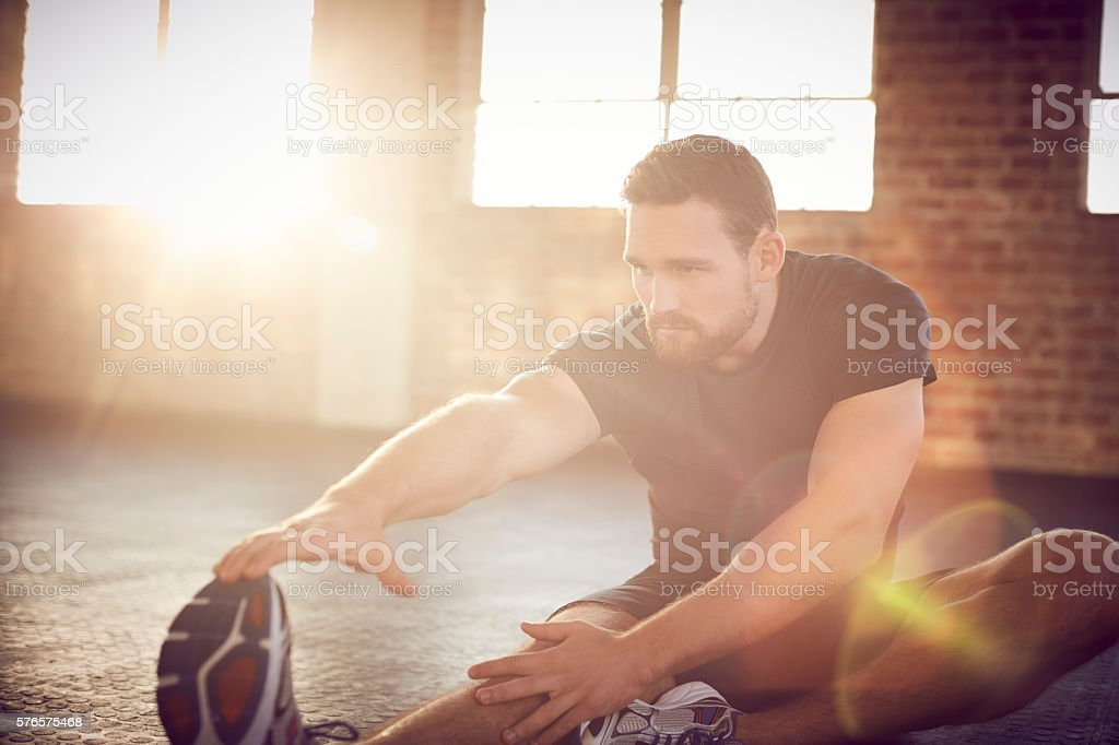 Young man performing stretching exercise in brightly lit gym stock photo