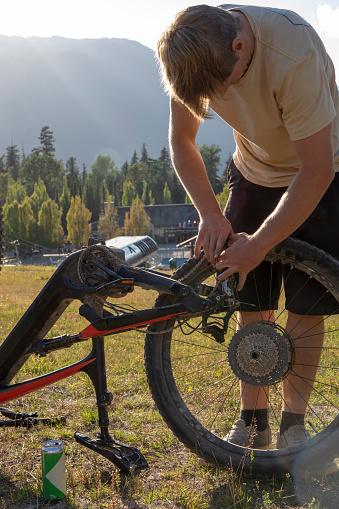 Young man performs bike mechanics on mountain e-bike in alpine meadow